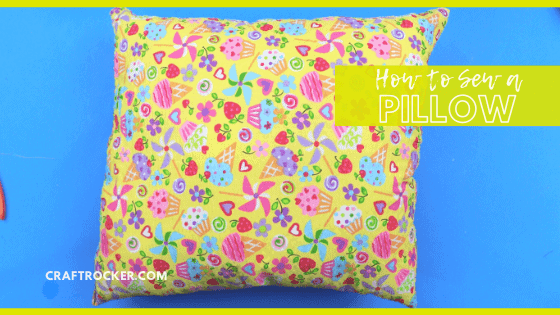 Close Up of Colorful Pillow on Blue Background with text overlay - How to Sew a Pillow - Craft Rocker