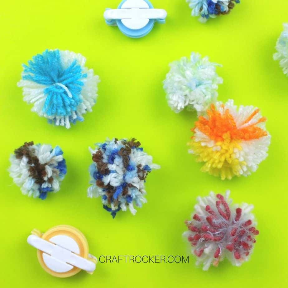 Colorful Pom Poms next to pom pom makers - Craft Rocker