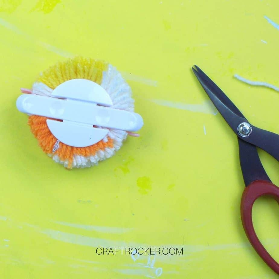 Cut yarn on pom pom maker next to scissors - Craft Rocker