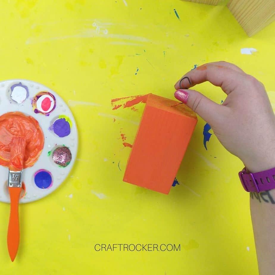 Hand Holding Orange Painted Wood Pillar - Craft Rocker