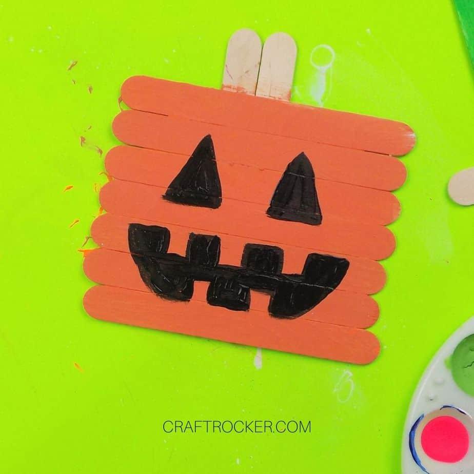 Jack-o-Lantern Face Painted on Orange Popsicle Sticks - Craft Rocker