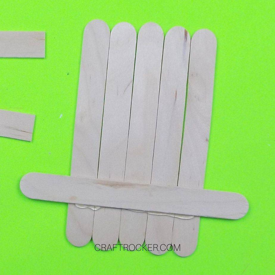 Popsicle Stick Glued Across Bottom of 5 Popsicle Sticks Lined Up next to Each Other - Craft Rocker