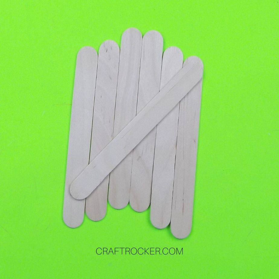Popsicle Sticks Lined Up with Another Stick Glued Diagonally Across Them - Craft Rocker
