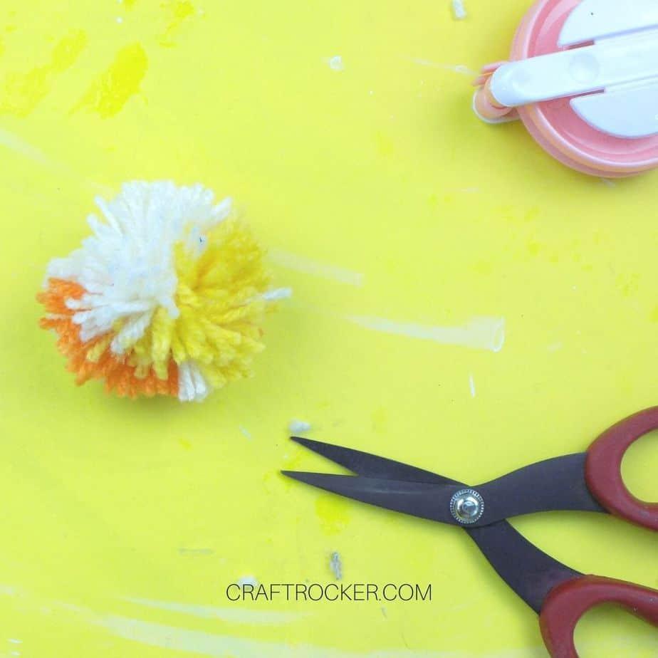 Small pom pom with trimmed edges next to scissors - Craft Rocker