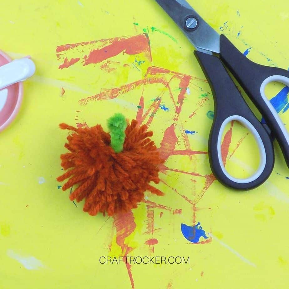 Close Up of Yarn Pumpkin Pom Pom next to Scissors - Craft Rocker