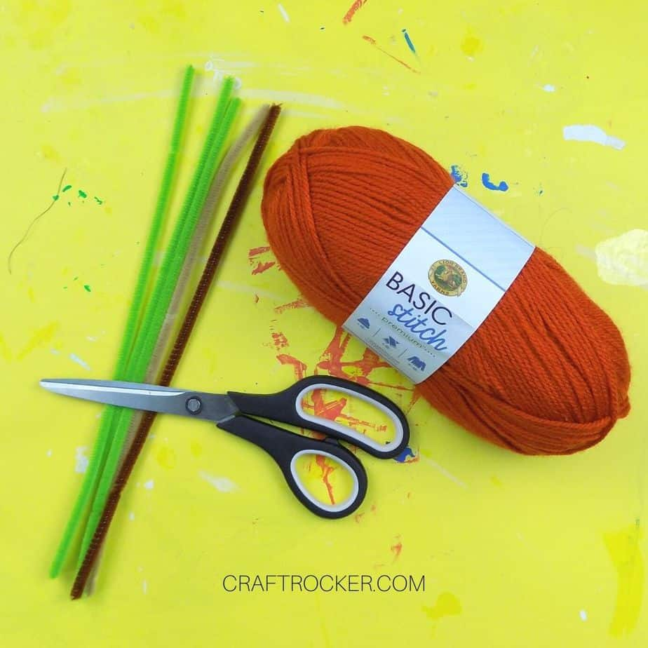 Orange Spool of Yarn next to Scissors and Pipe Cleaners - Craft Rocker