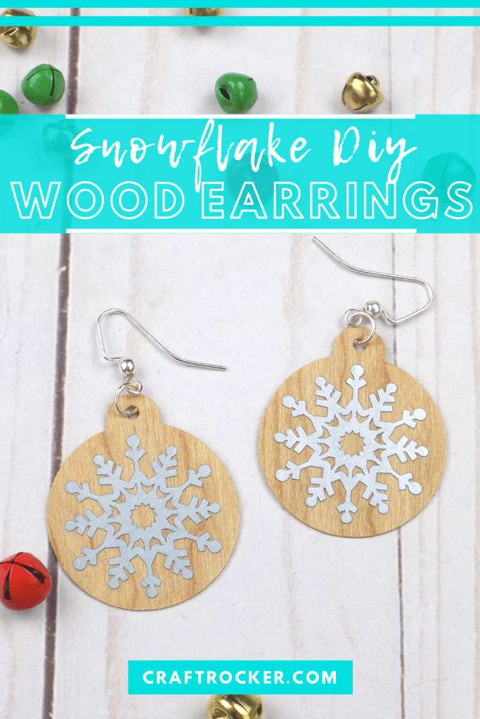 Close Up of Christmas Earrings next to Bells on Wood Background with text overlay - Snowflake DIY Wood Earrings - Craft Rocker