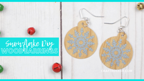 Close Up of Christmas Earrings on Wood Background with text overlay - Snowflake DIY Wood Earrings - Craft Rocker