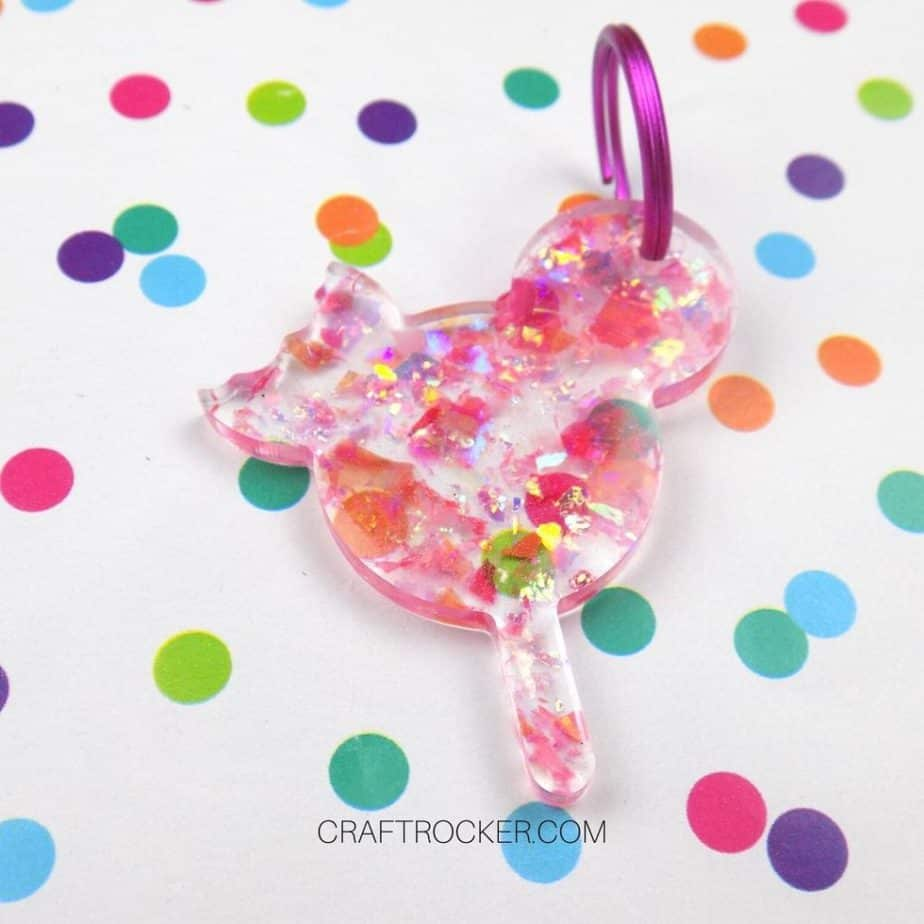 Close Up of Glitter Resin Mickey Popsicle Keychain on Wood Background - Craft Rocker
