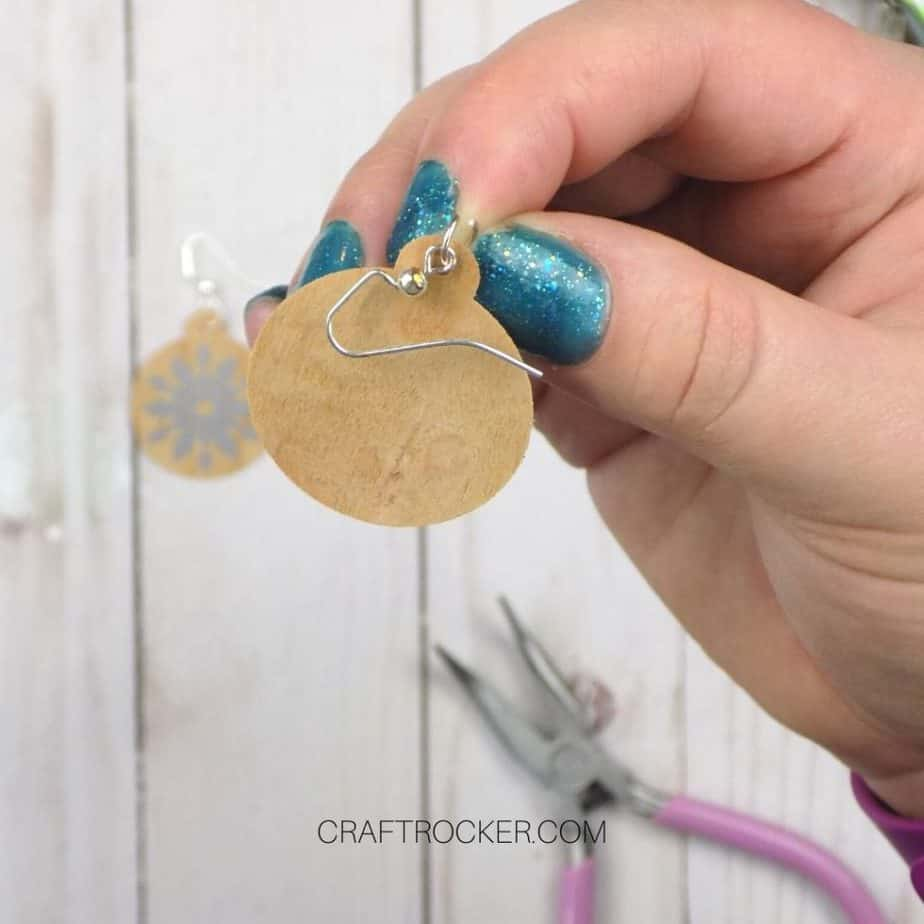 Close Up of Hand Holding Wood Ornament with Jump Ring and Fishhook Earring Attached - Craft Rocker