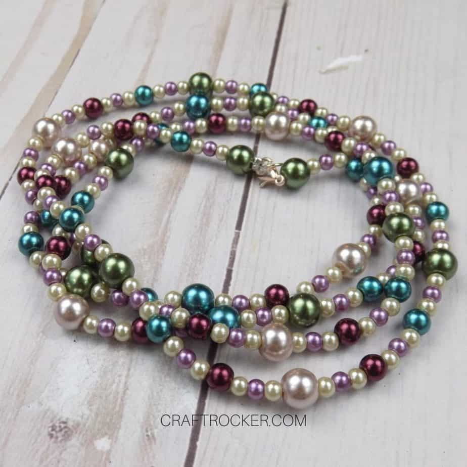 Close Up of Long Beaded Necklace on Wood Background - Craft Rocker