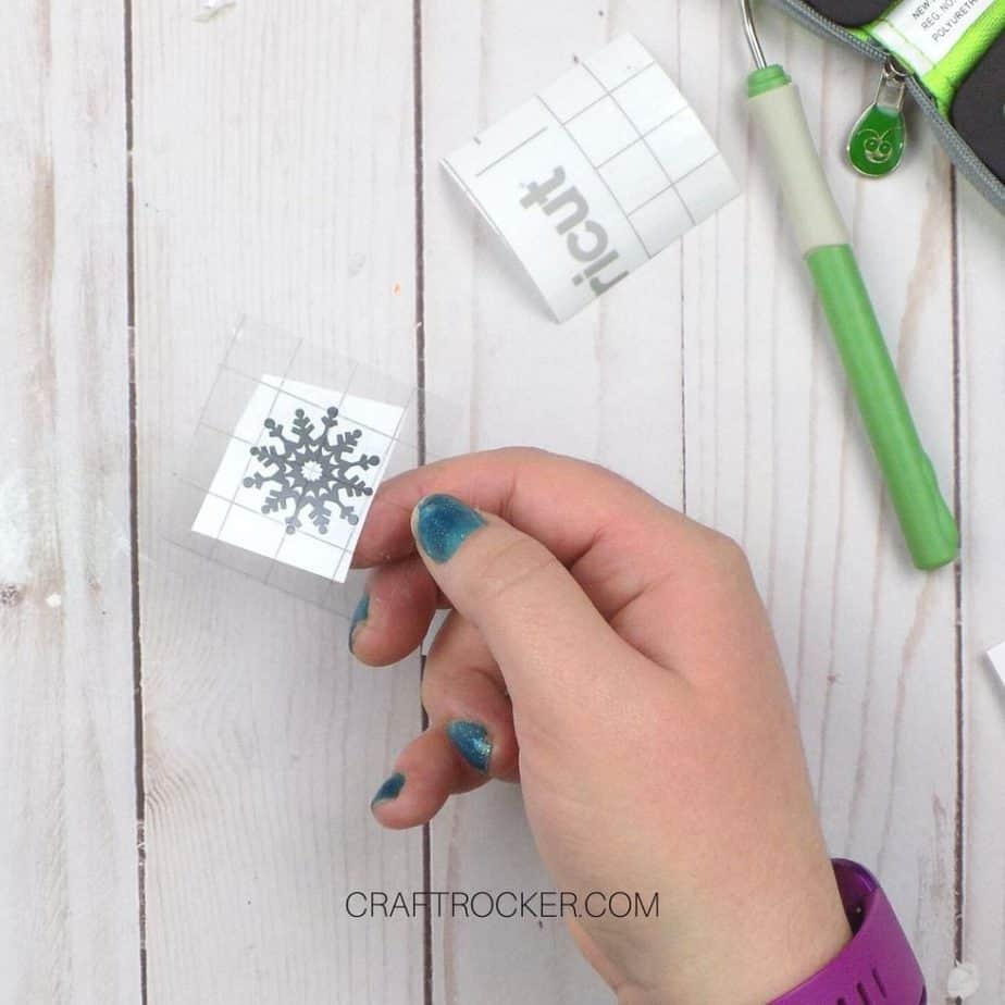 Hand Holding Transfer Tape On Silver Snowflake - Craft Rocker