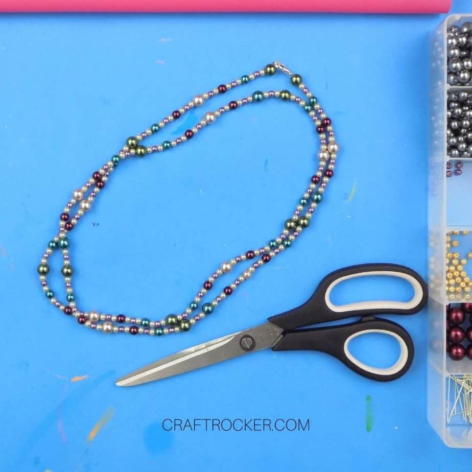 Long Beaded Necklace Next to Scissors - Craft Rocker