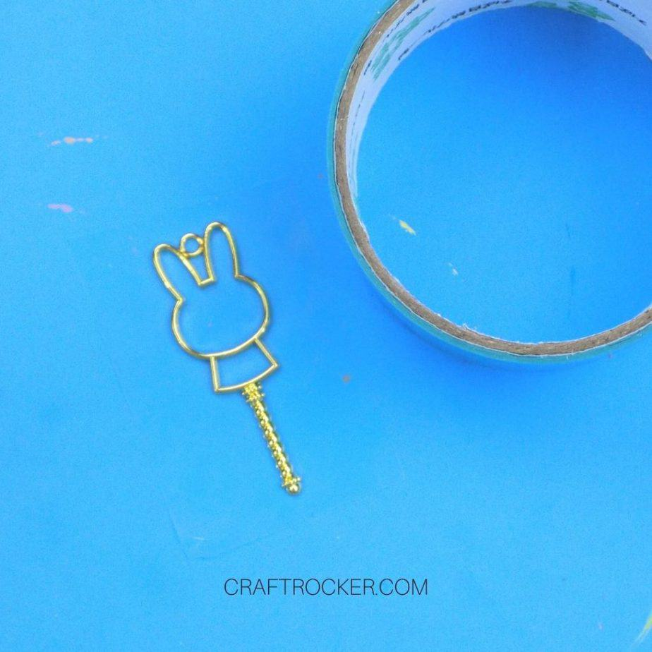 Metal Charm Attached to Tape next to Roll of UV Resin Tape - Craft Rocker