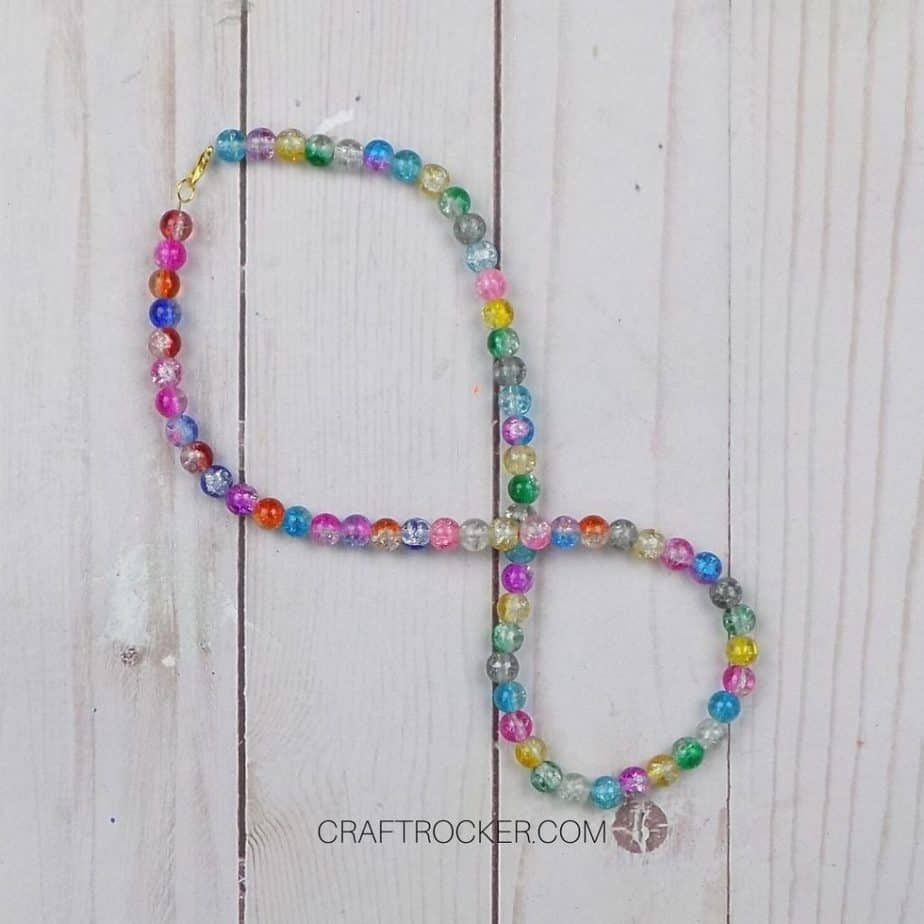 Twisted Colorful Beaded Necklace on Wood Background - Craft Rocker