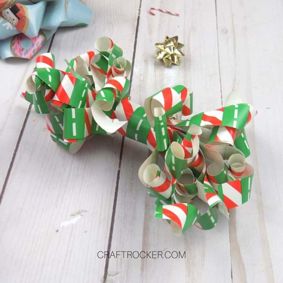 Close Up of Curled Wrapping Paper Bow on Wood Background - Craft Rocker