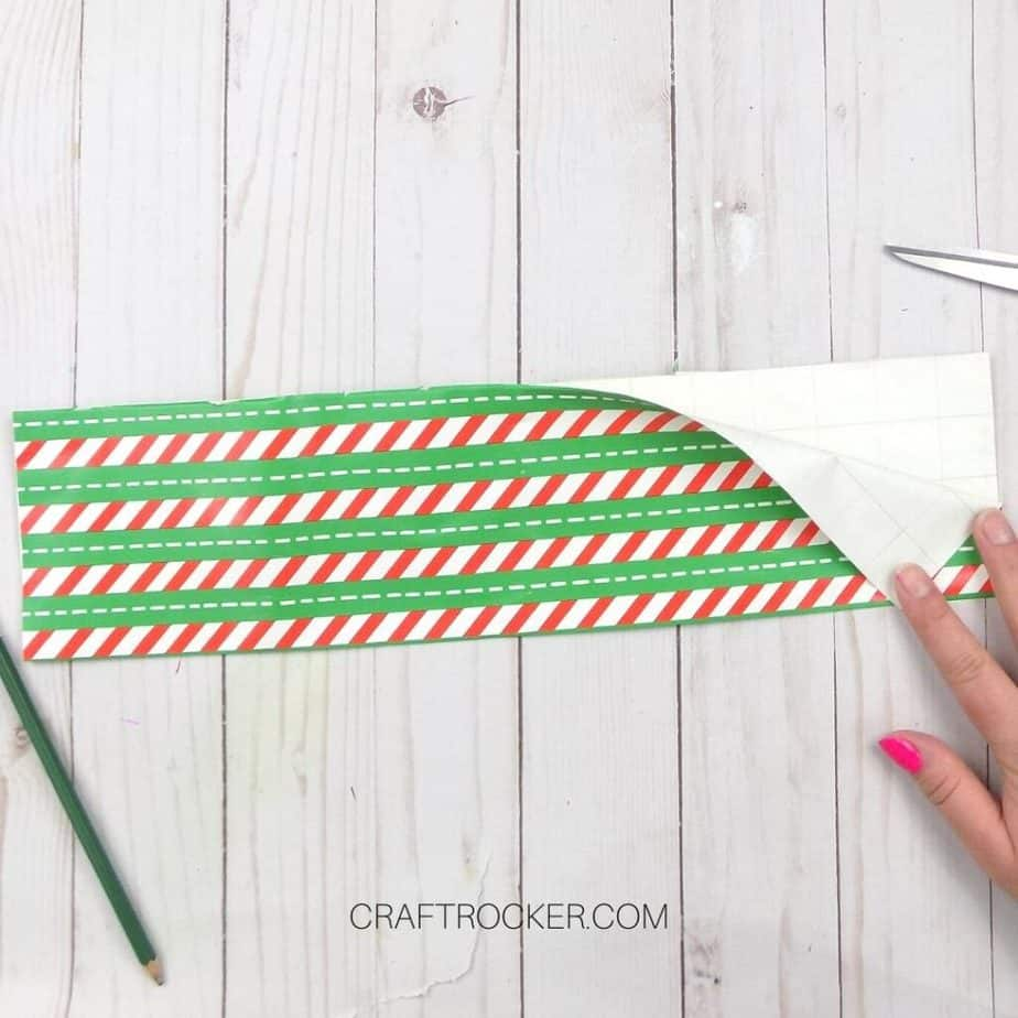 Hand Holding Back Corner of Folded Striped Piece of Wrapping Paper - Craft Rocker