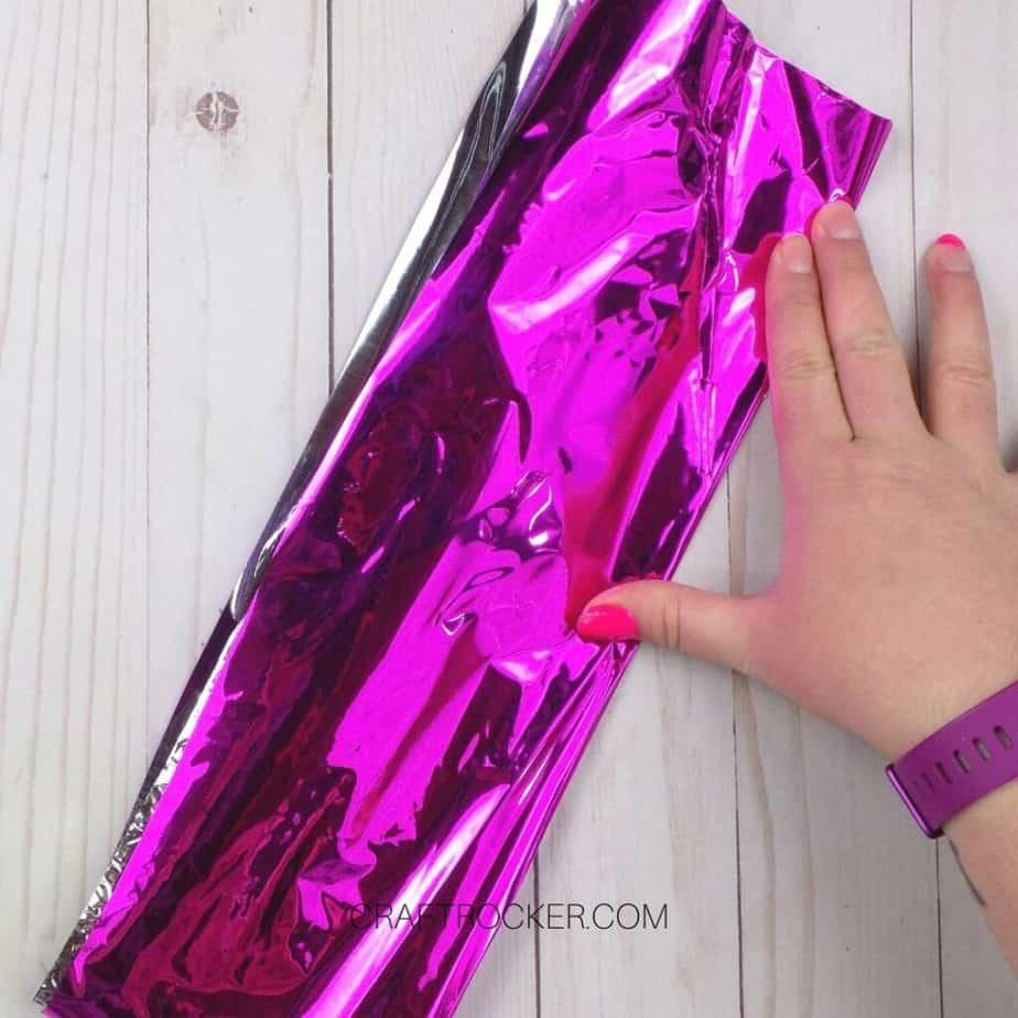 Hand Holding Folded Piece of Pink Foil Paper - Craft Rocker