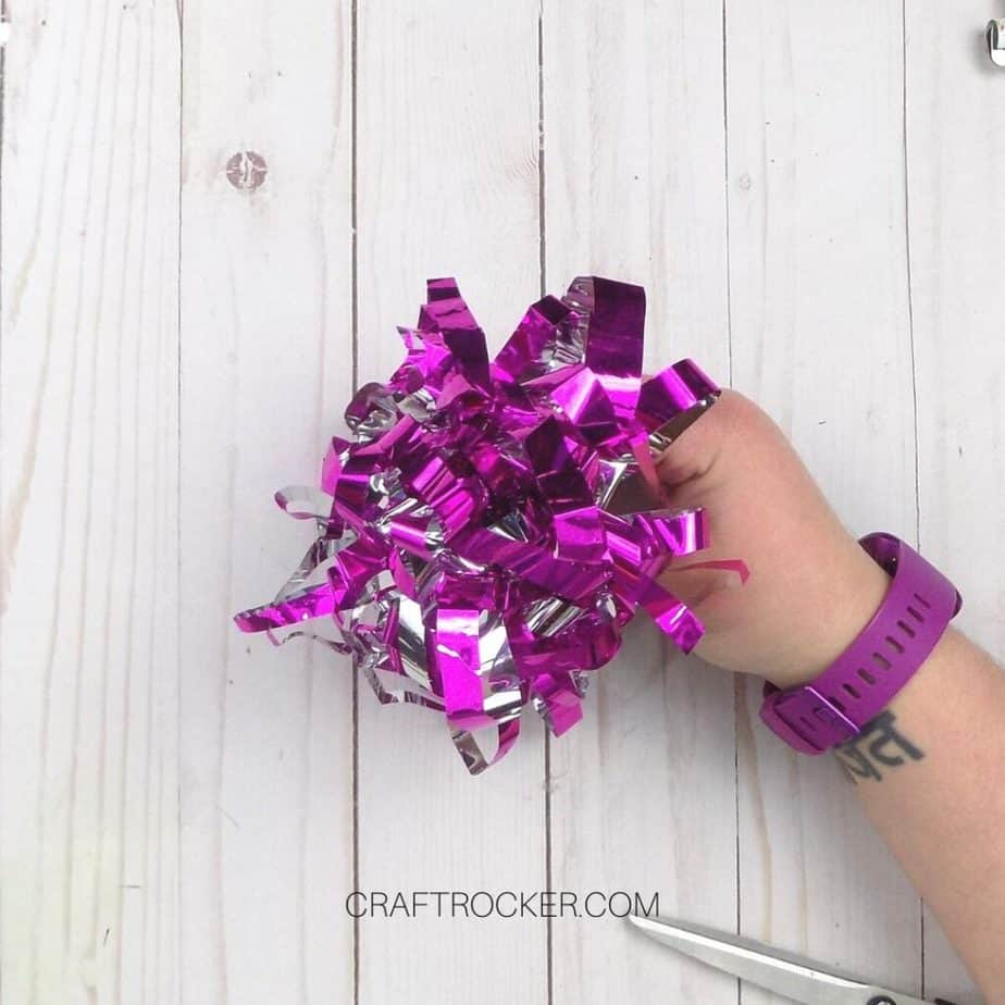 Hand Holding Fringed Wrapping Paper Bow - Craft Rocker