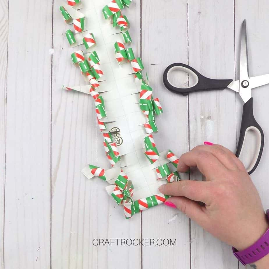 Hand Rolling End of Curled Wrapping Paper next to Scissors - Craft Rocker