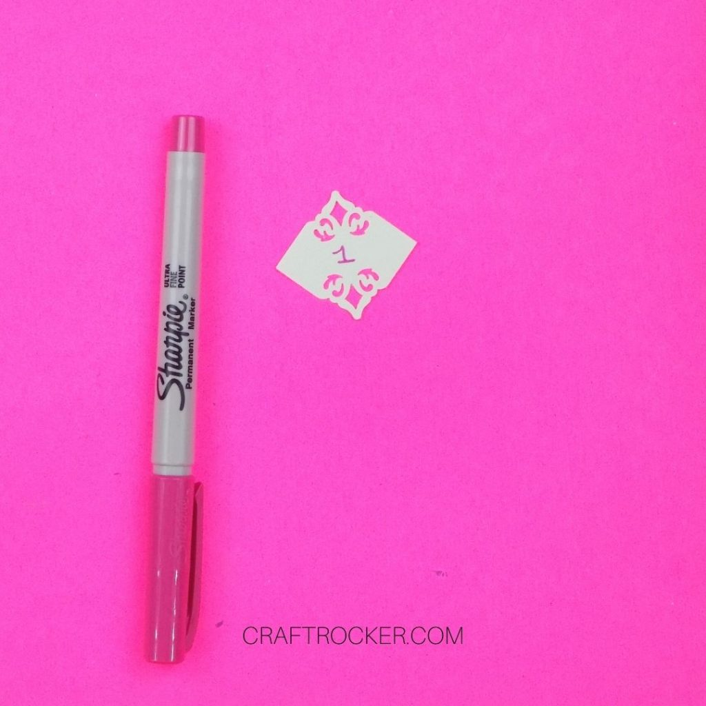 Sharpie Marker Next to Decorative Square with the Number 1 Written on It - Craft Rocker
