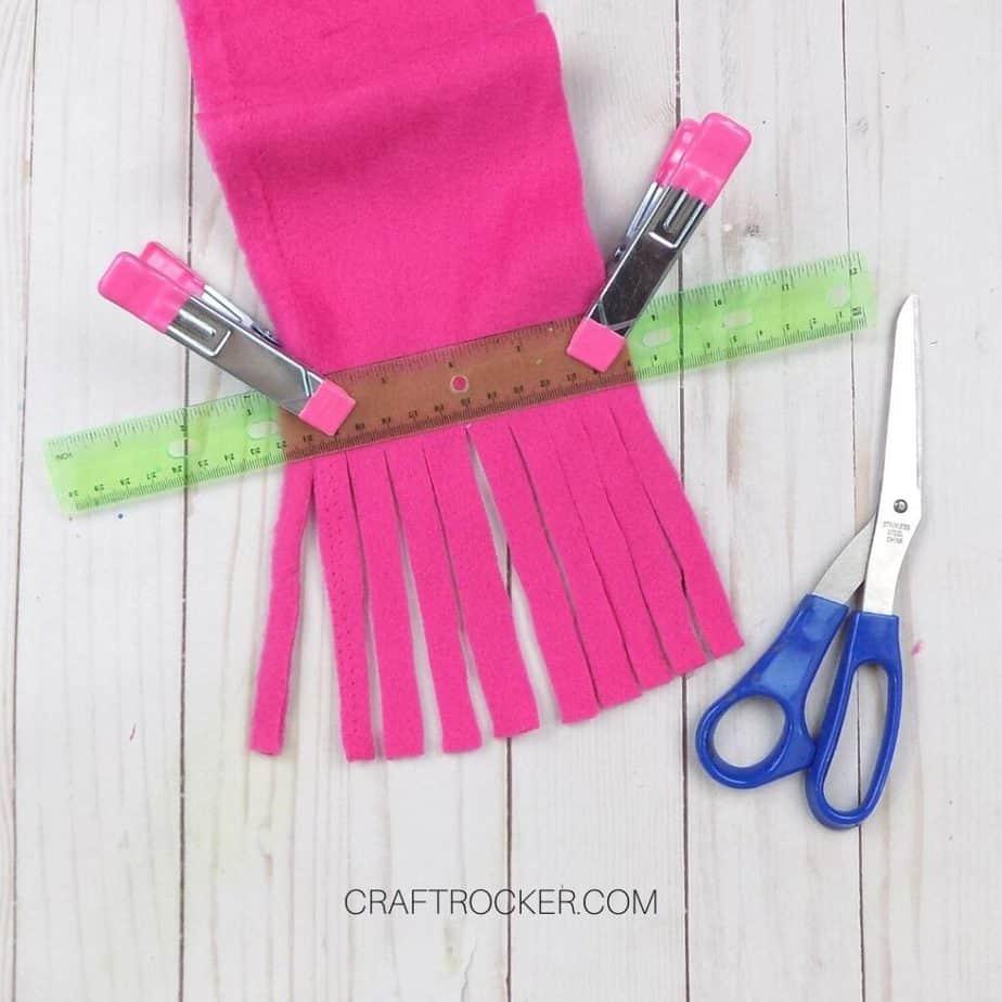 Close Up of Fringe Cut into Hot Pink Fleece next to Scissors - Craft Rocker