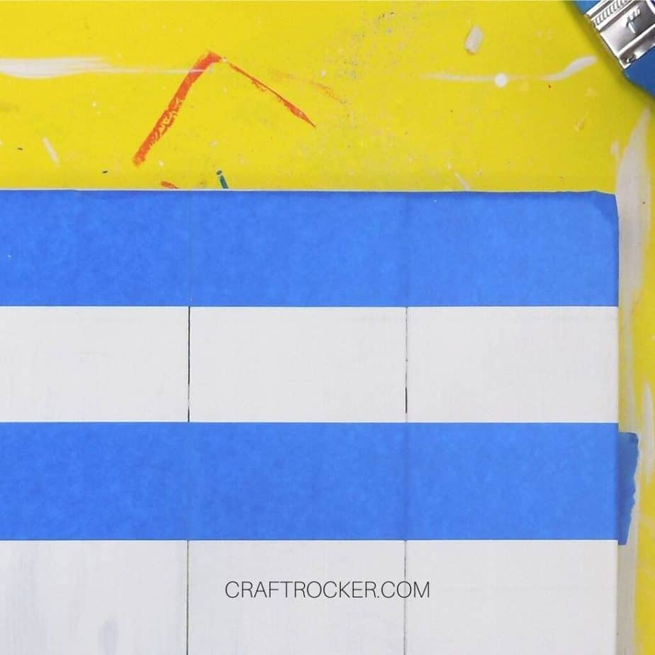 Close Up of Horizontal Lines of Blue Tape on White Pallet - Craft Rocker