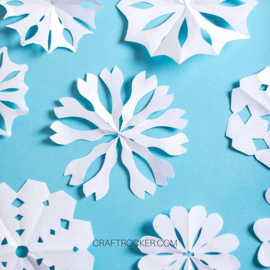 Different Styles of Paper Snowflakes on Blue Background - Craft Rocker