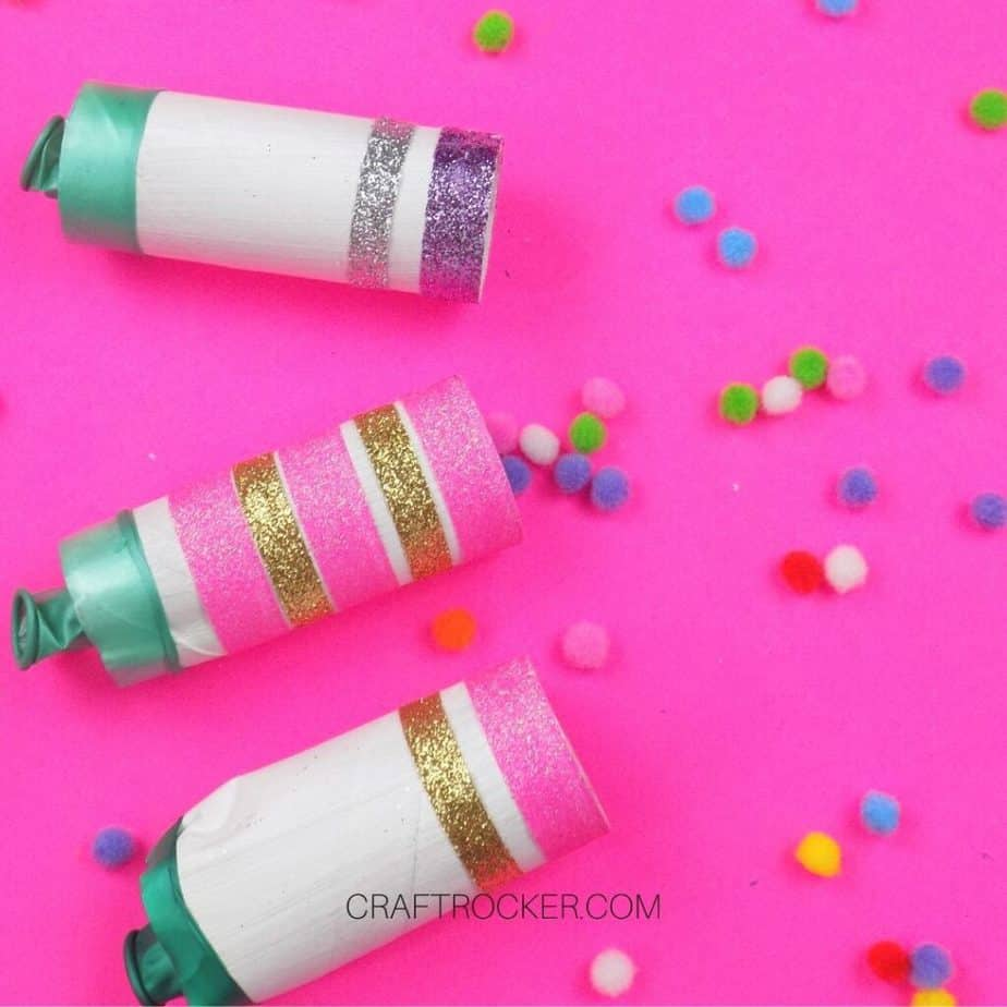 Glitter New Years Poppers on Pink Background next to Pompoms - Craft Rocker