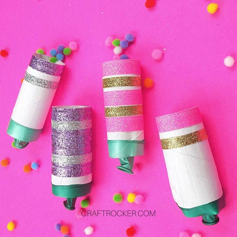 Glittery DIY New Years Poppers on Pink Background next to Pompoms - Craft Rocker