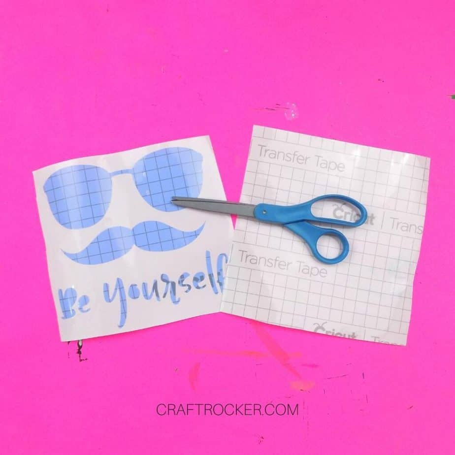 Scissors on top of Be Yourself Vinyl Stencil and Transfer Tape - Craft Rocker