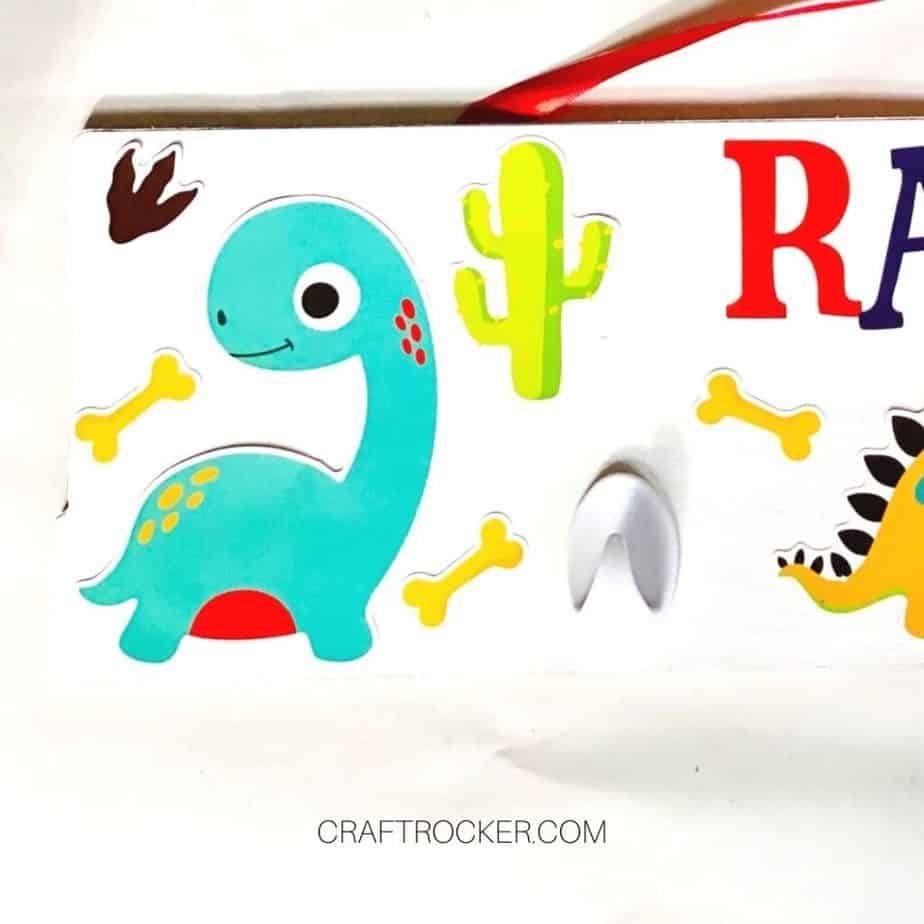 Small Stickers next to Dinosaur on Wood Sign - Craft Rocker
