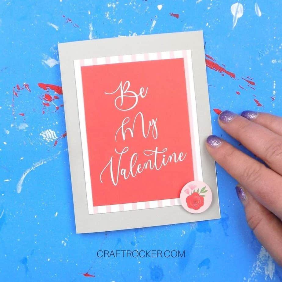Hand Holding Greeting Card with Matted Be My Valentine and Rose Embellishment Attached to Front - Craft Rocker