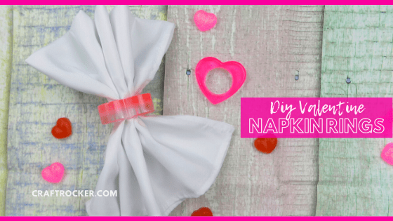 White Napkin in a Heart Napkin Ring next to Pink Heart Napkin Ring on Wood Background with text overlay - DIY Valentine Napkin Rings - Craft Rocker