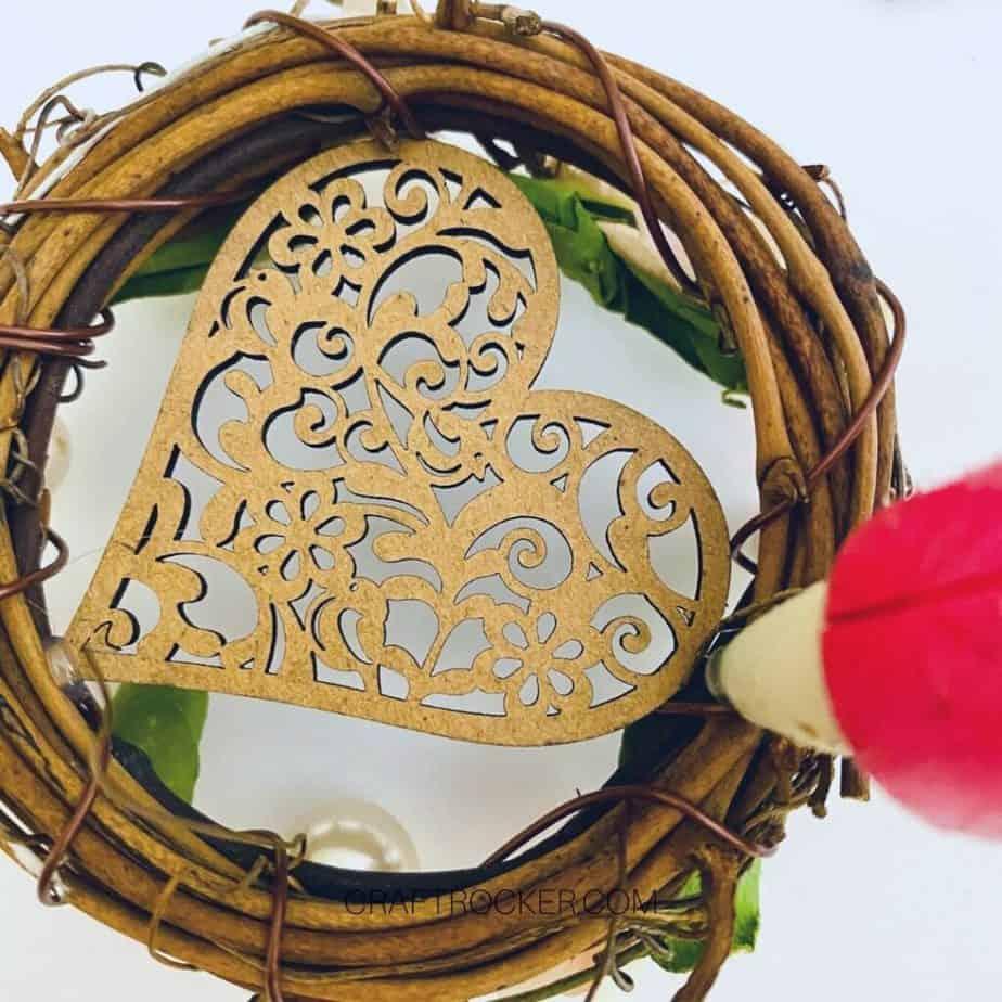 Close Up of Glue Gun Adding Hot Glue to Back of Decorated Wreath - Craft Rocker