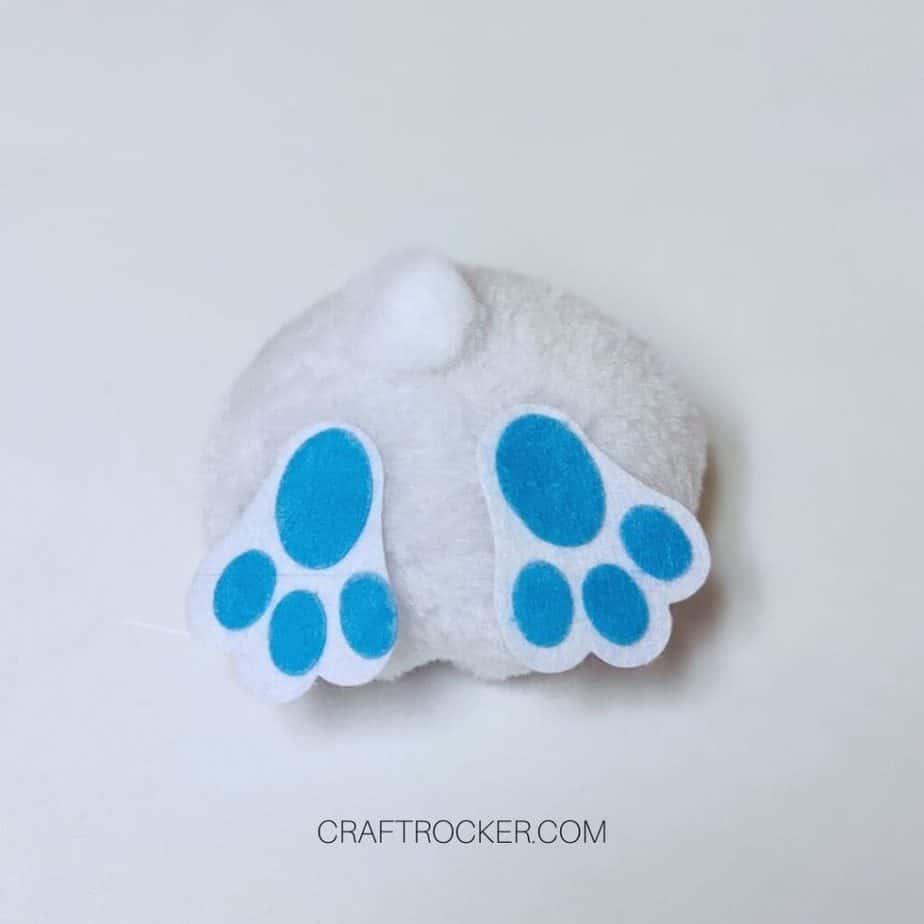 2 Blue Bunny Feet Glued to Bottom of Large Pompom - Craft Rocker