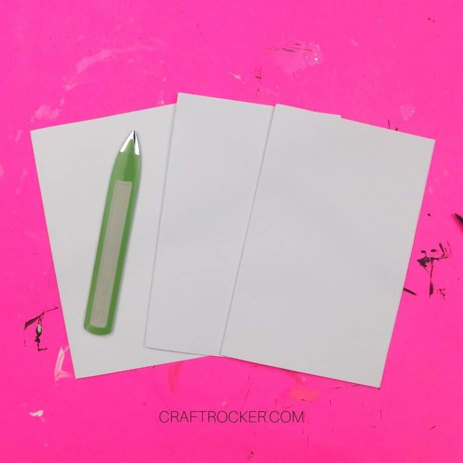3 Folded Stacks of Plain White Paper with Bone Folder on Top - Craft Rocker