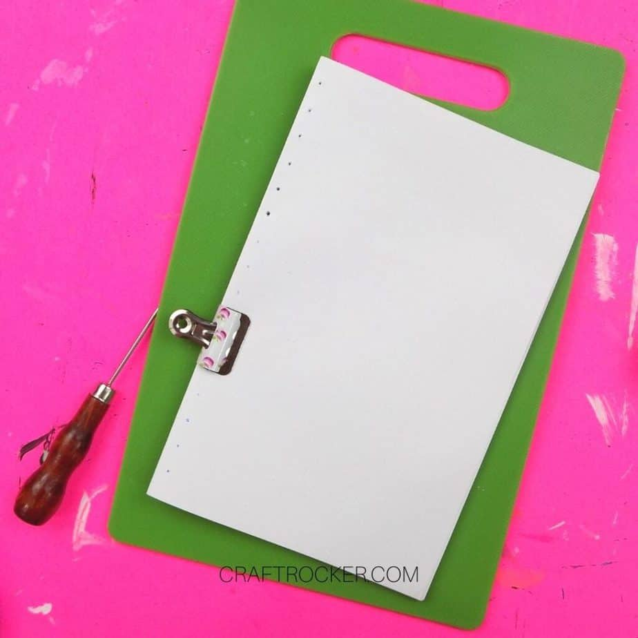 Awl Next to Binder Clipped Folded Papers on Cutting Board - Craft Rocker