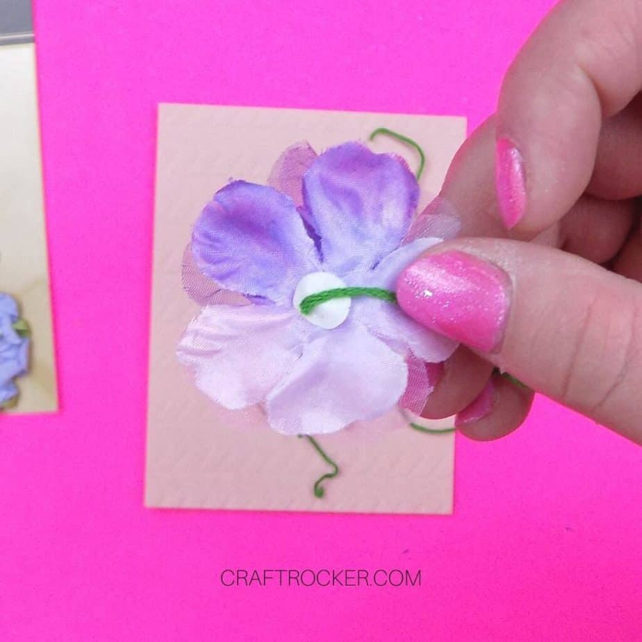 Close Up of Hand Holding Flower Sticker with Green Floss Attached - Craft Rocker