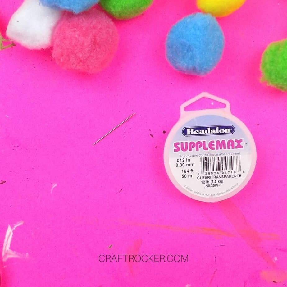 Close Up of Sewing Needle next to Roll of Clear Beading Thread - Craft Rocker