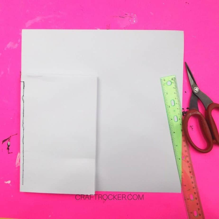 Sewn Stack of Papers on 12x12 Cardstock next to Ruler and Scissors - Craft Rocker