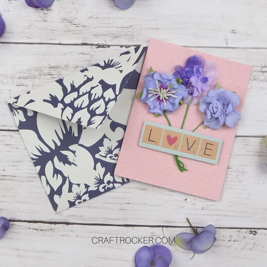 Close Up of Handmade Paper Envelope and Card Next to Flowers on Wood Background - Craft Rocker