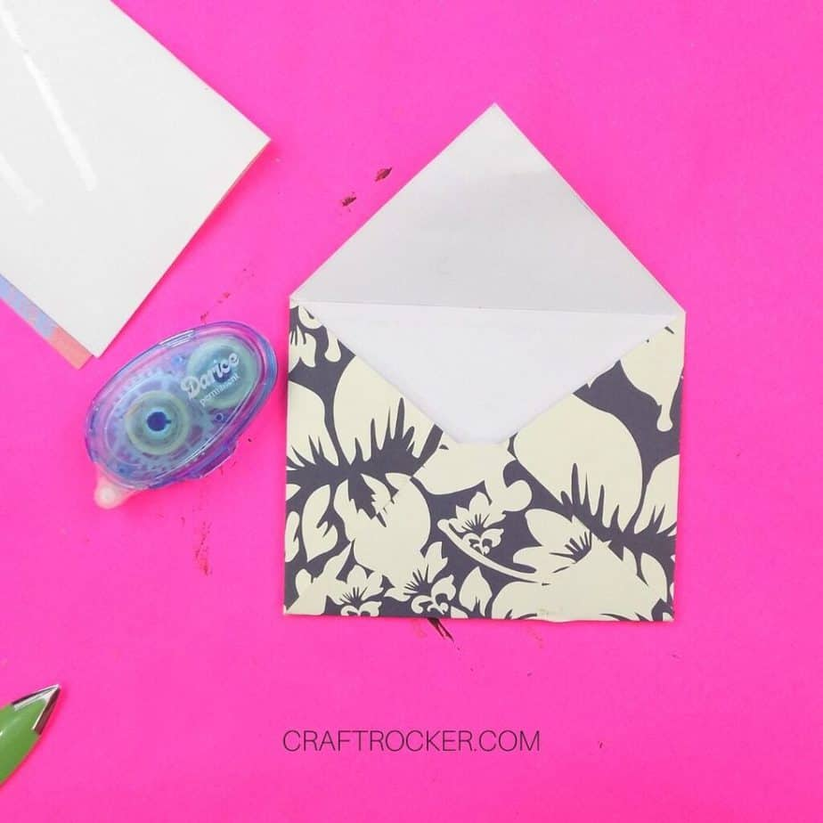 Decorative Cardstock Envelope next to Glue Runner on Pink Background - Craft Rocker