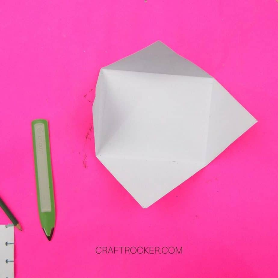 White Diamond Cardstock with Folded Edges next to Bone Folder on Pink Background - Craft Rocker