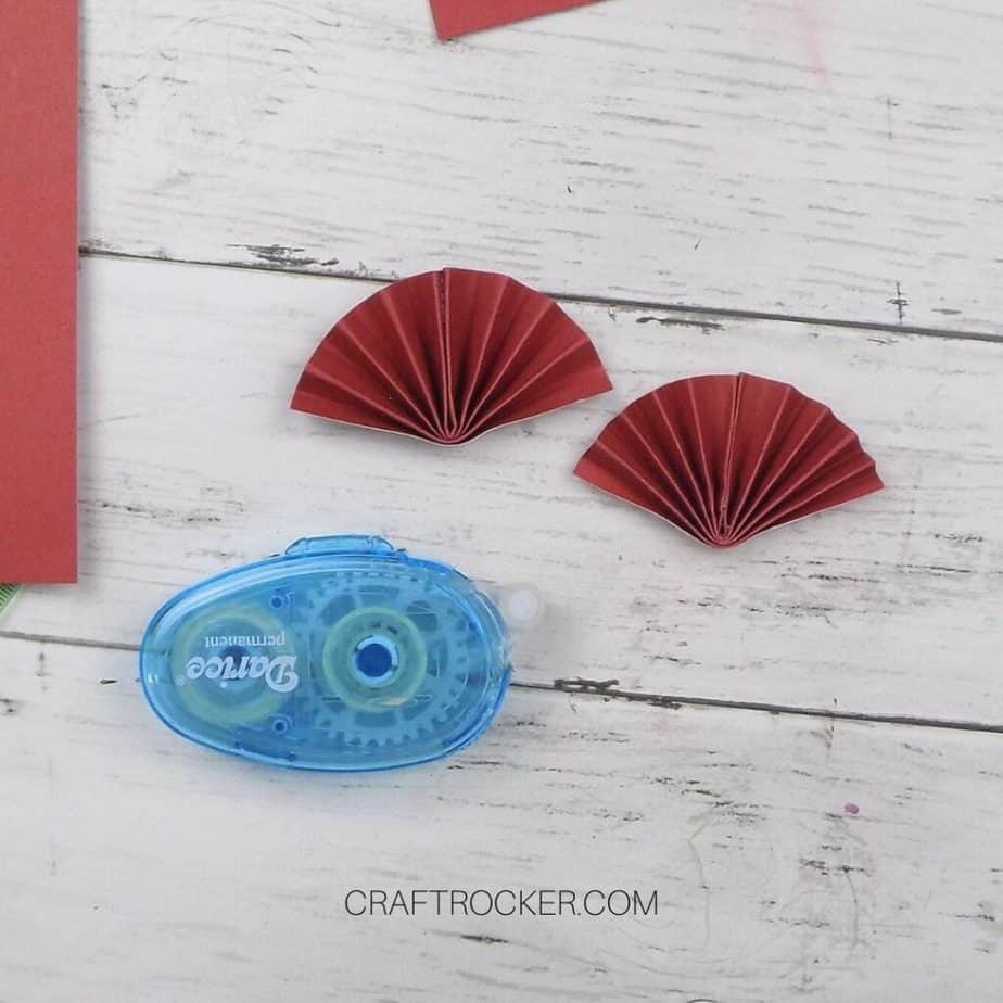 Close Up of 2 Small Red Paper Fans next to Glue Runner - Craft Rocker