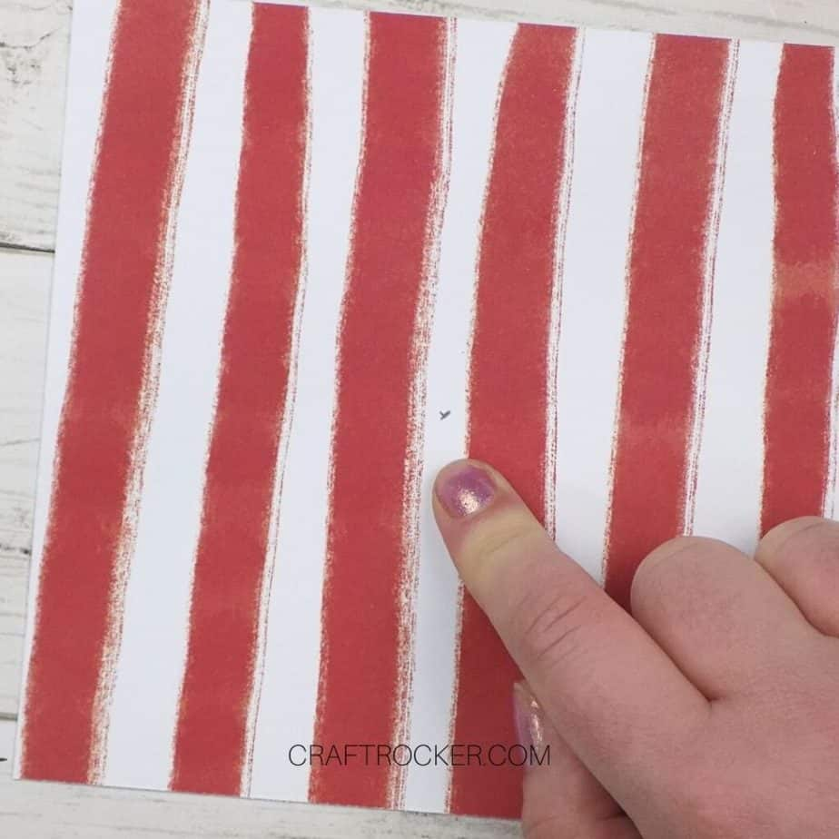 Close Up of Finger Pointing to Marked Center of Red and White Striped Paper - Craft Rocker