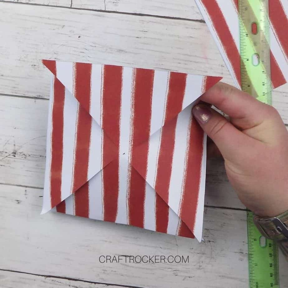 Hand Holding Diagonally Cut Piece of Red and White Striped Paper - Craft Rocker