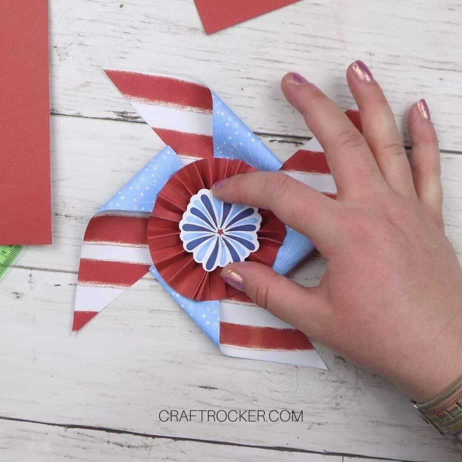 Hand Putting Sticker on Red Paper Rosette Pinwheel - Craft Rocker