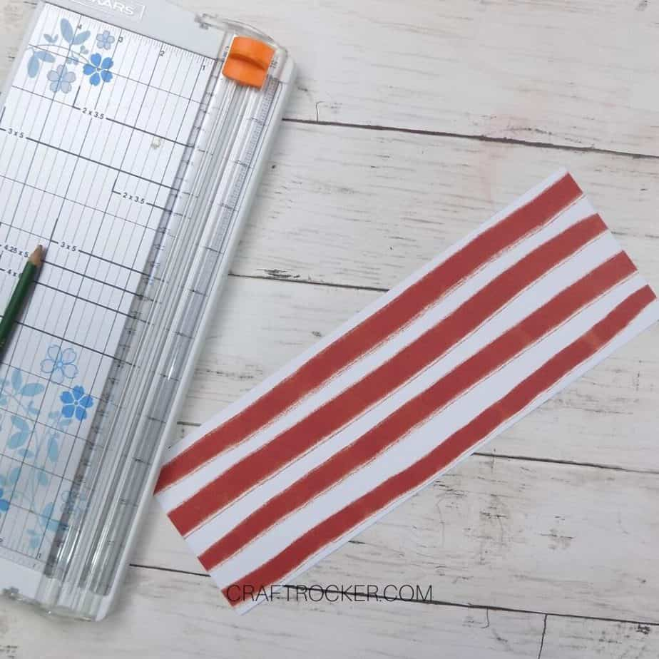 Piece of Striped Cardstock next to Paper Cutter - Craft Rocker